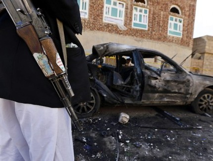 A Houthi member standing beside a car destroyed in the suicide attack targeting a mosque | © epa european pressphoto agency b.v. / Alamy