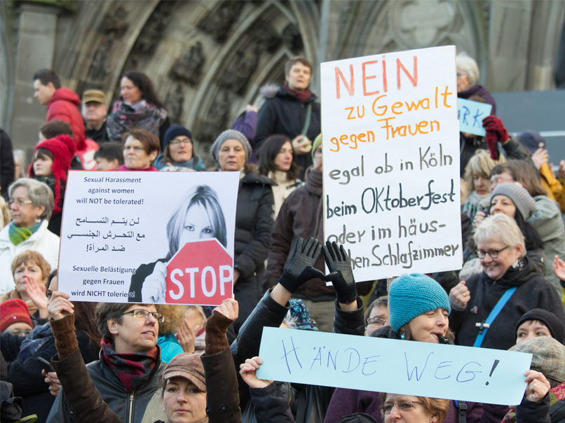 Protesters gather outside Cologne Cathedral with a sign reading