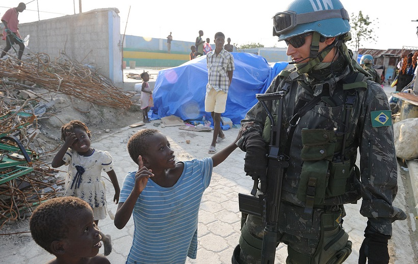 A Brazilian U.N. peacekeeper walks with Haitian children - (cc) US Navy, David A. Frech