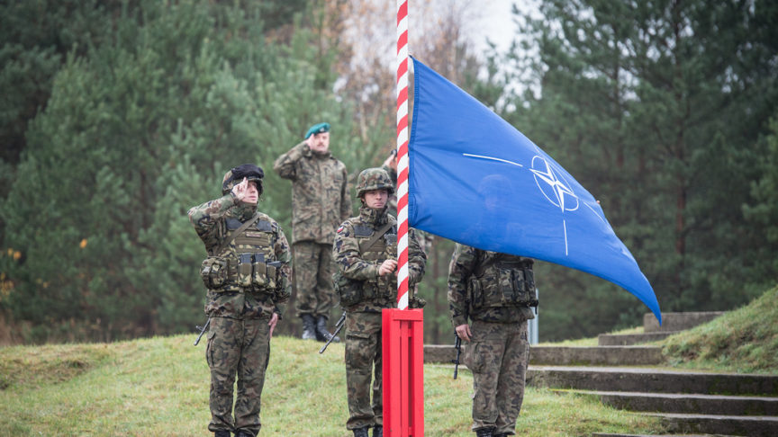 Four US soldiers salute the NATO flag as it's raised