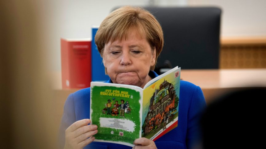 Chancellor Angela Merkel reads a brochure on the German constitution