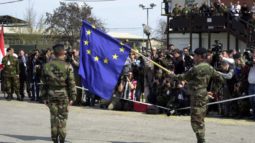 Two soldiers hold a large flag of the EU