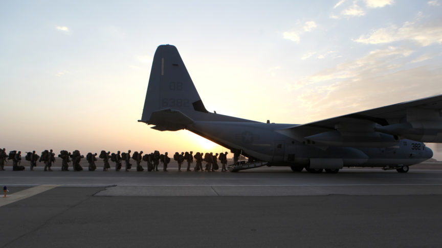A line of marines boarding a plane after a mission