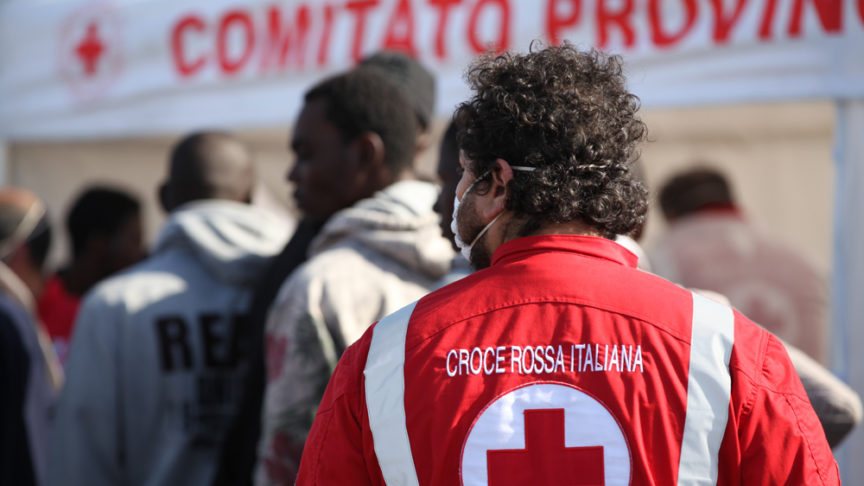 A member of the Italian red cross stands on a pier next to a group of migrants