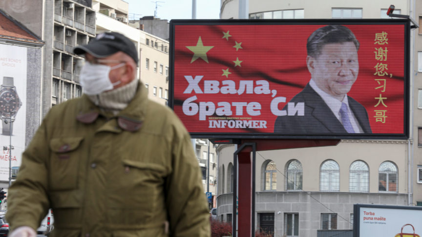 """A man wearing a protective mask passes by a billboard depicting Chinese President Xi Jinping as the spread of the coronavirus disease (COVID-19) continues in Belgrade, Serbia, April 1, 2020. The text on the billboard reads """"Thanks, brother Xi""""."""