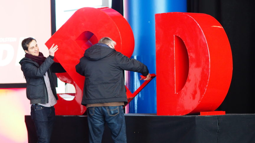 Two men take apart a giant SPD sign at a party conference