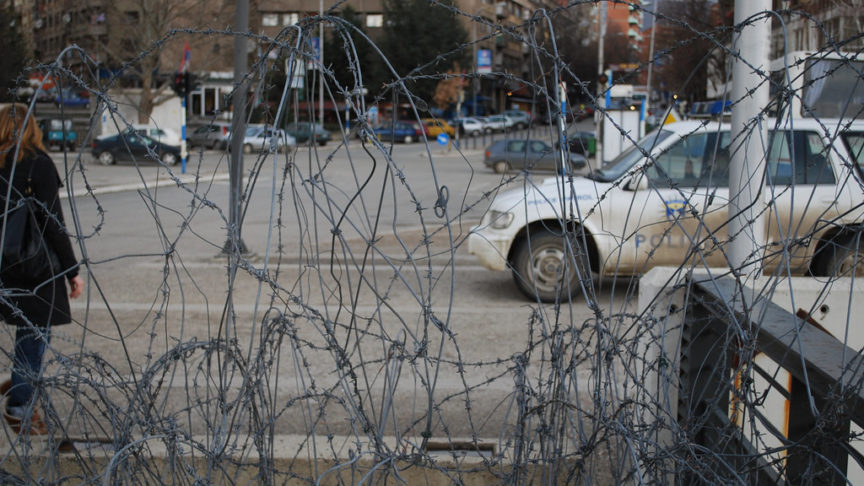 Barbed wire in front of a police car in North Mitrovica