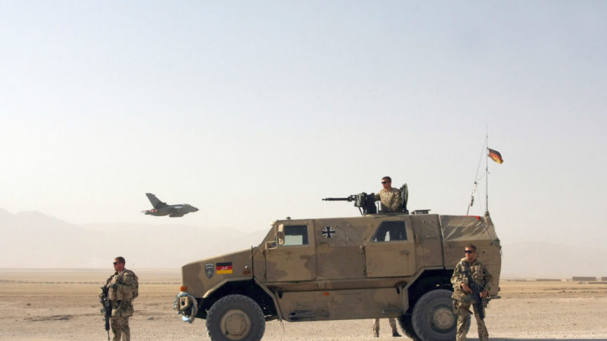 German troops and a combat vehicle stand in front of a fighter plane taking off
