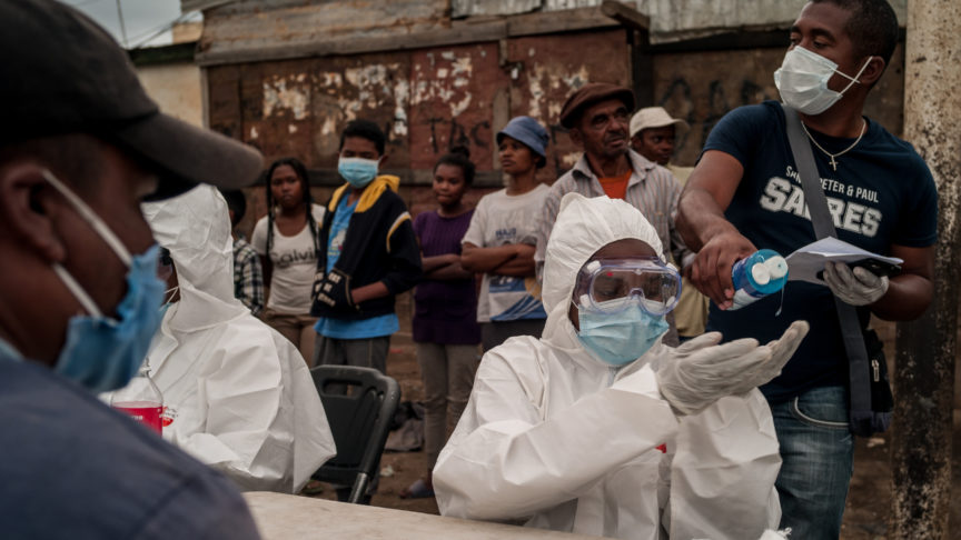 A medical worker in Madagascar in full PPE sanitises their hands while testing people for covid/19