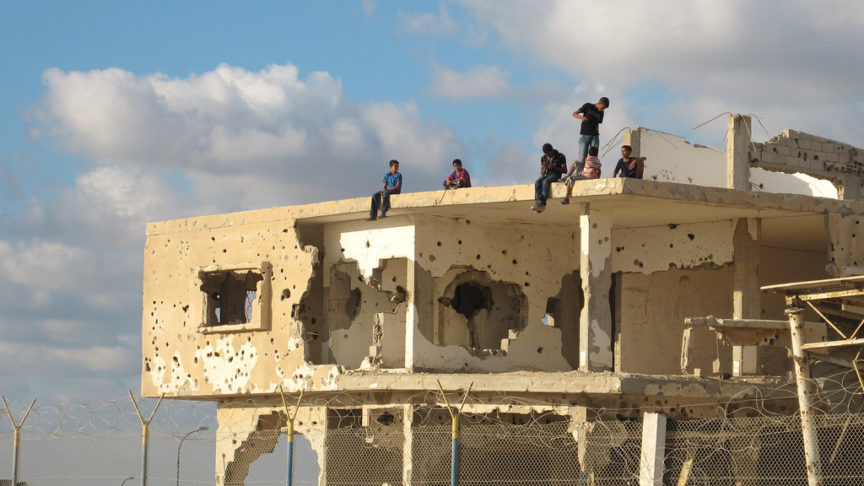 Children sit on top of a destroyed building in Gaza