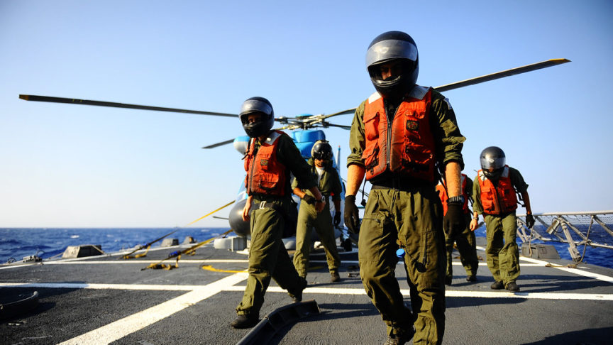 A Greek and Israeli helicopter crew step onto an aircraft carrier