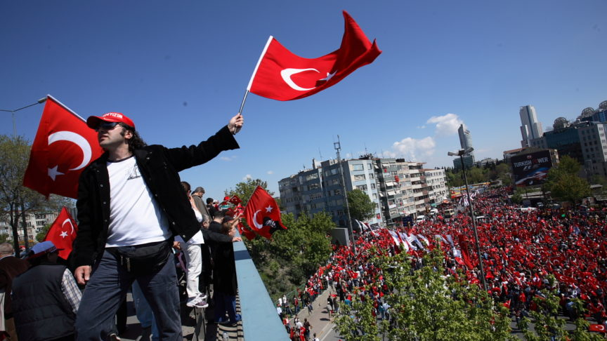 A man on a rooftop waves a Turkish flag above a square full of protestors