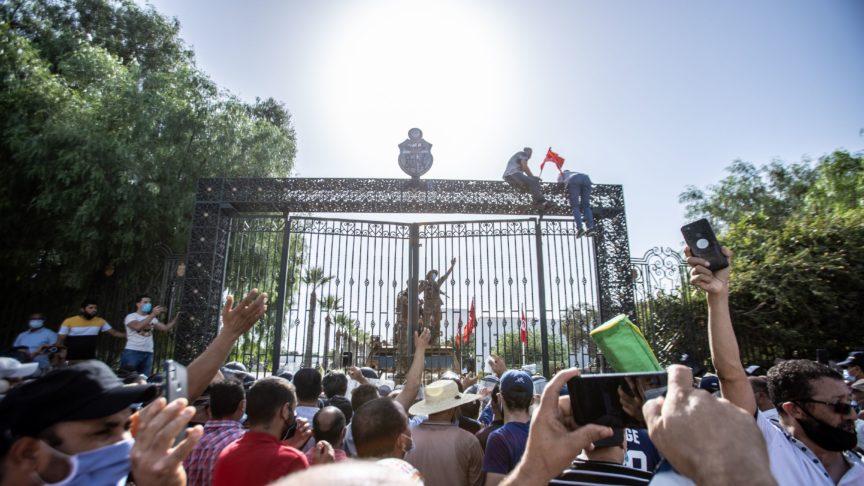 Protestors in Tunisia scale the gates of a government complex